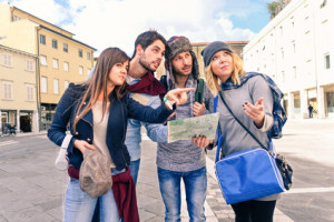 Group of tourists looking map - Couples of best friends in holiday lost in old town center -  Young students seek information on road map in city square - Concept of friendship tourism and education